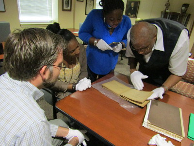 Dr. Cooper and the team examine one of Carver's notebooks.